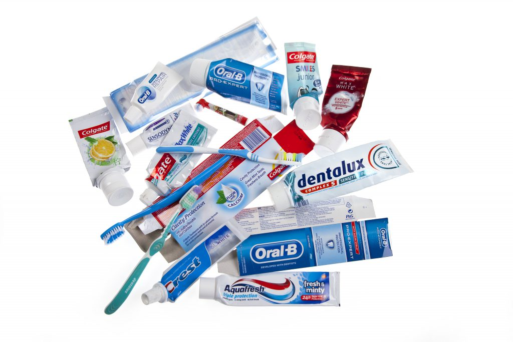 photo of tooth brushes and empty tooth paste tubes